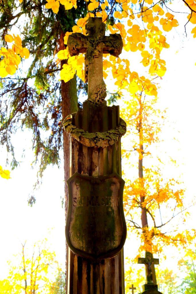 Grób Masalskich z widocznym kartuszem w postaci herbu.